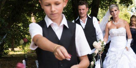 Frisch vermähltes Brautpaar mit Blumenjunge